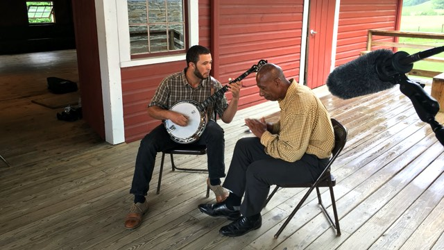 an older male clogging dancer seated on a rainy front porch with a banjo player, framed by sound equipment in the foreground