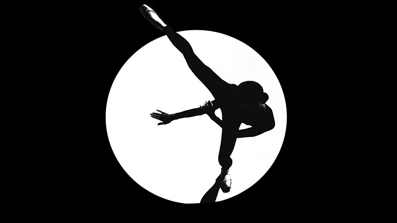a black and white silhouette of a ballet dancer in a spotlight extending her leg in to the side and her hands forward