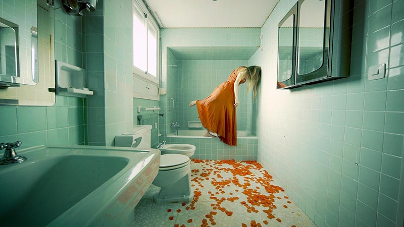 a woman dressed in orange, in a teal colored bathroom, with orange rose petals covering the floor