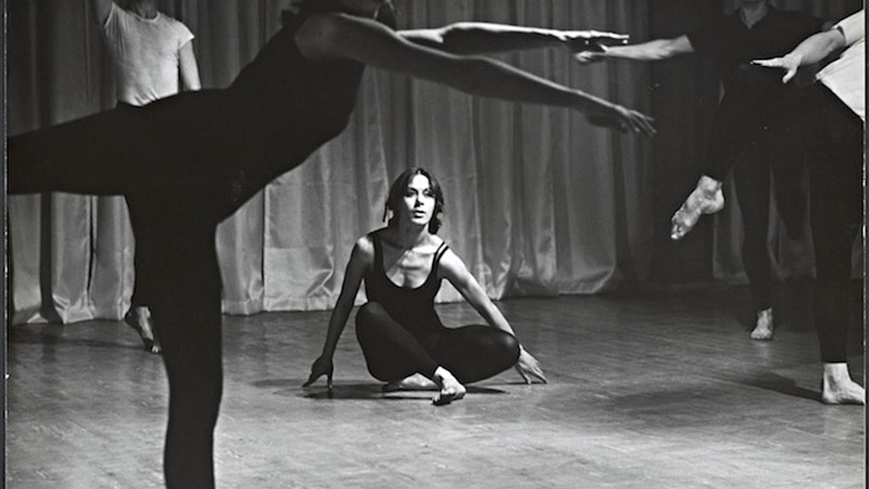 a historic photo of dancer/choreographer Yvonne Rainer from the 1960s in which she is seated with legs crossed, framed by the legs and feet of other dancers, all in black dancewear