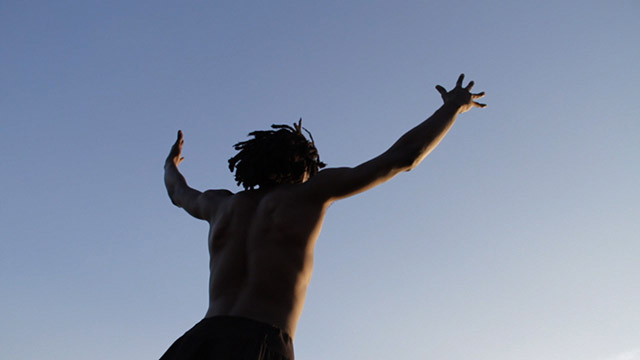 a single male dancer looking up and throwing his arms up at a blue sky