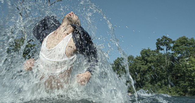 a light skinned male dancer jumps out of splashing water