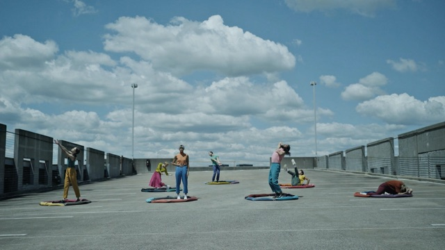 seven dancers are encircled by fabric sculptures on a parking garage roof