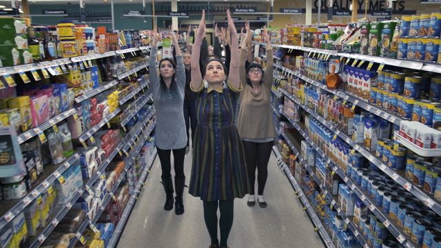 several dancers reach their arms upward, filling a grocery store aisle