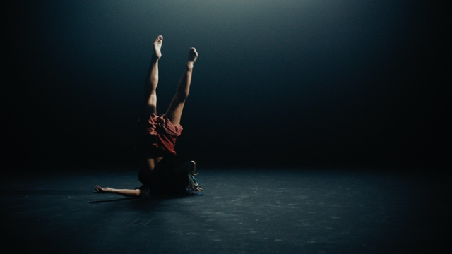 a dancer balances precariously on her shoulder, with her feet toward the sky