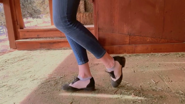 a pair of legs in jeans and clogs on a dirty barn floor