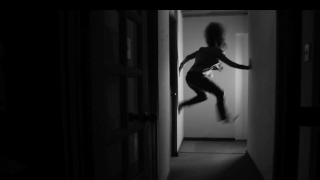 a dancer's silhouette in mid-jump at the far end of a hallway
