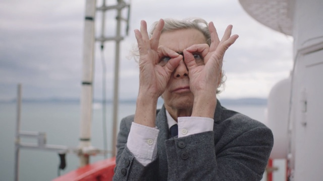 an older man with light skin looks through his hands, shaped like glasses