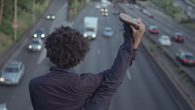 a dancer holds a leg above his head, looking down at a freeway
