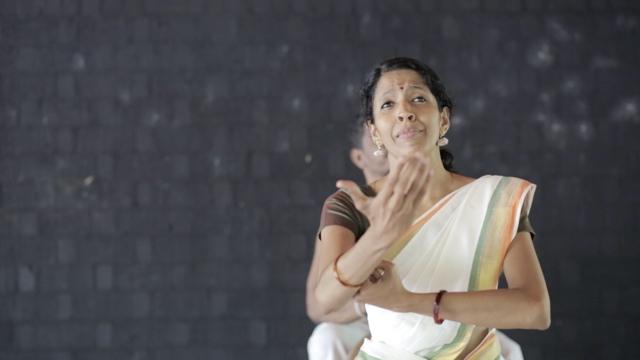 an Indian dancer emotes dramatically, reaching an arm toward the camera