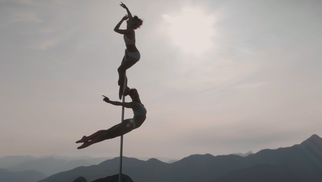two dancers on a pole reach high and wide, set against a mountain backdrop