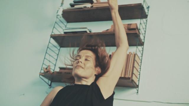 a light skinned woman with hair in mid-flight swings an arm upward