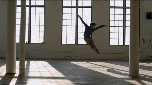an Asian American man in mid air in a balletic jump