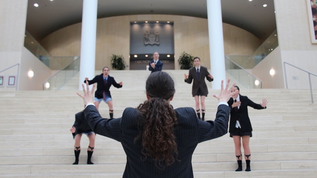 several women in men's suit jackets, ties, and underwear, on the steps of a building gesture wildly