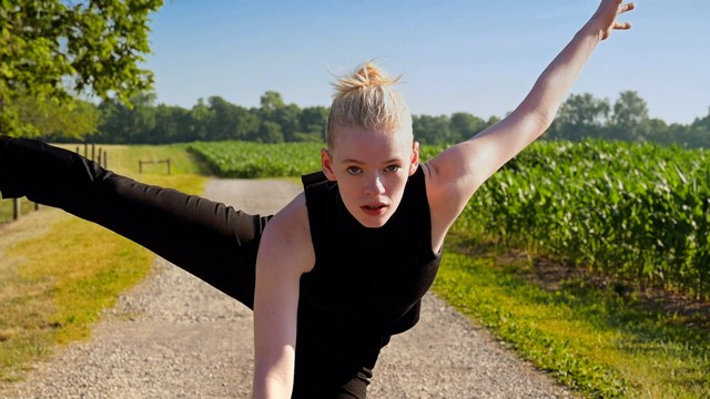 a light skinned dancer with blonde hair stares at the camera with arm and leg outstretched