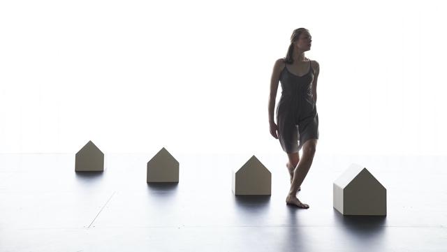 a light skinned woman walks between miniature houses