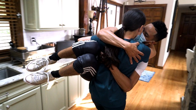 a light skinned woman carries a dark skinned man through a kitchen