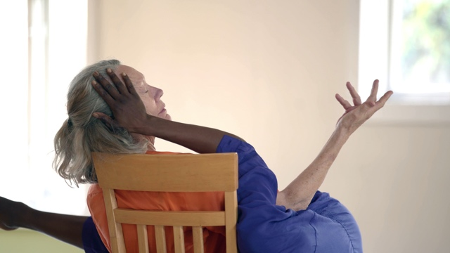 an older white woman in a chair closing her eyes, with a younger black woman touching her face