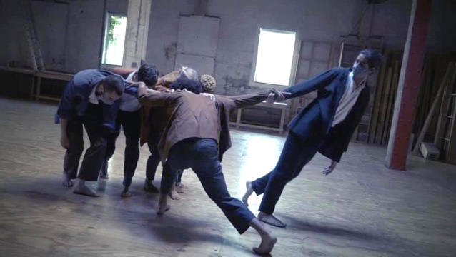 one dancer holds a hand, leaning away from the group