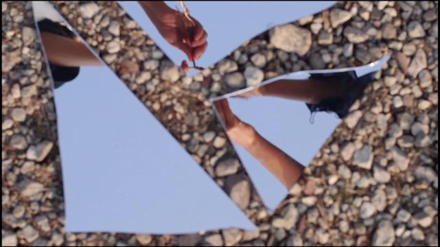 broken pieces of a mirror reveal a dancer's hands above