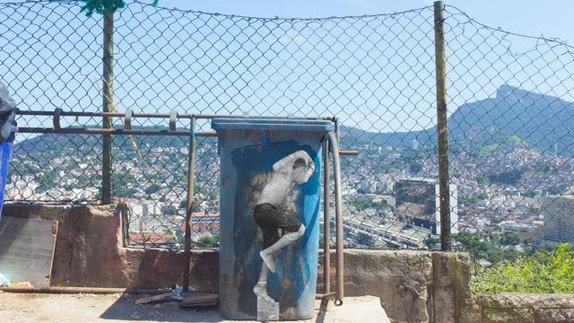 a cutout photograph of a boy dancing, superimposed on a dumpster in front of a mountain city landscape