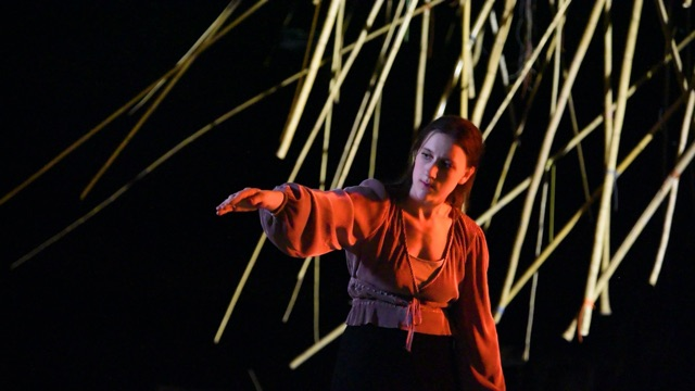 a dancer in a flowy shirt reached an arm out to the side, in front of a sculpture of abstract lines