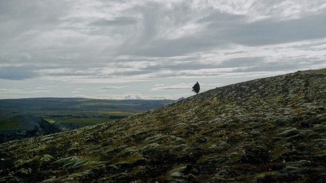 a single person in the distance on the side of a hill, clouds swirling above