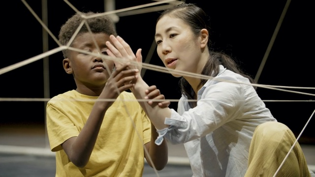 an Asian woman and a black boy dance with hands in a maze of string