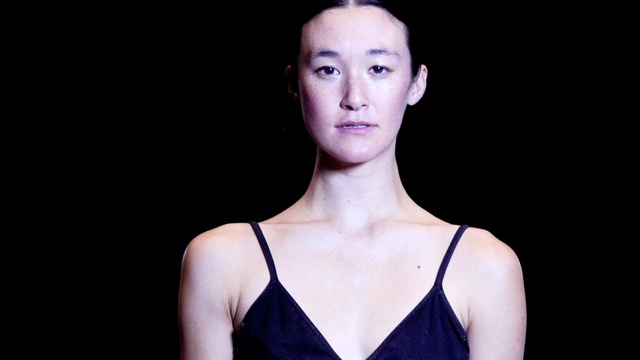 an Asian American dancer in a black top stares at the camera
