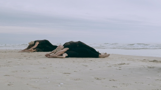two piles of dancers lying on top of one another on the beach