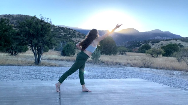 a dancer stretches an arm forward and leg back, twisting toward the sunset