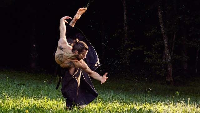 a bare chested white male dancer reaches toward the grass with a leg thrown up behind him