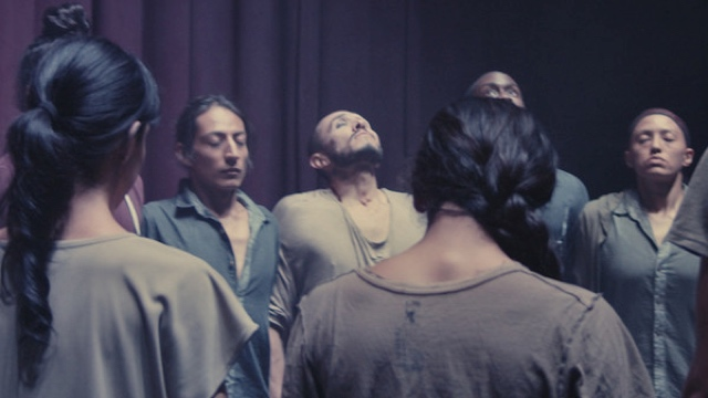 a group of male and female dancers with eyes closed, holding hands, mid-breath
