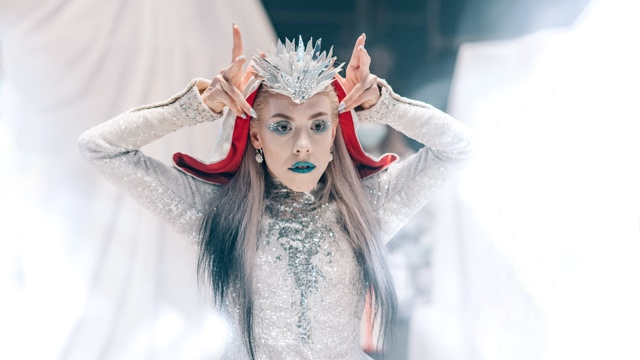 a dancer in an elaborate sparkling dress and crown wearing green lipstick
