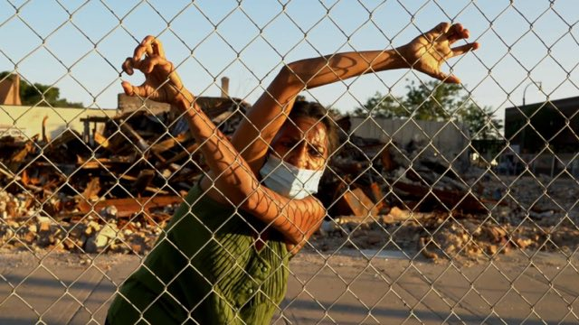 a brown-skinned woman with a mask hangs on and looks through a fence