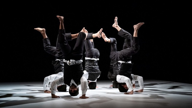 5 b-boys in headstands form a circle