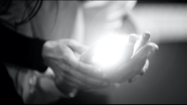 two pairs of light skinned hands cupping a ball of light