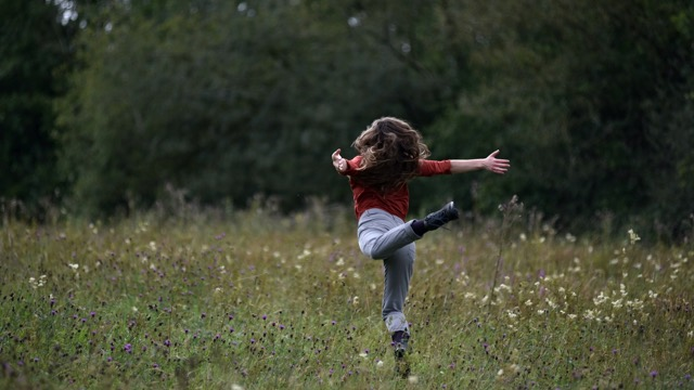 a dancer with jeans and boots leaps through a flowery meadow