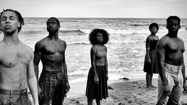 five dark skinned dancers stand in the sand at the beach with eyes closed