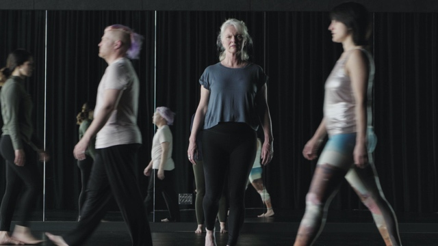 an older woman with white hair looks at the camera, while other dancers around her blur out of focus