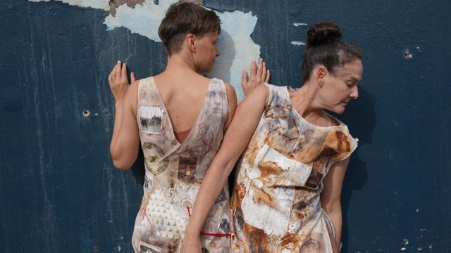 two light skinned dancers in fabric print dresses press against a wall