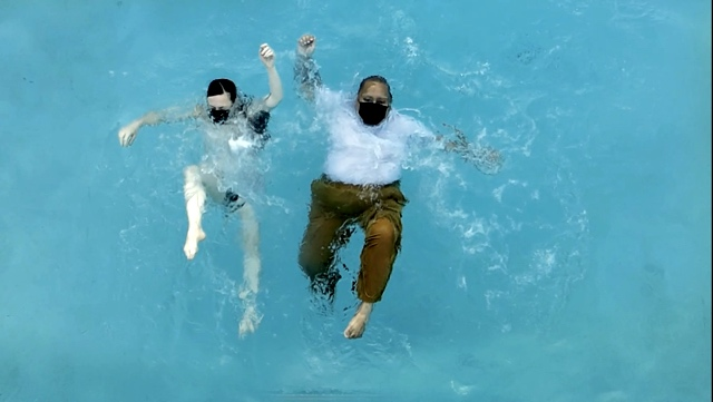 two dancers falling backward into a pool as waves ripple