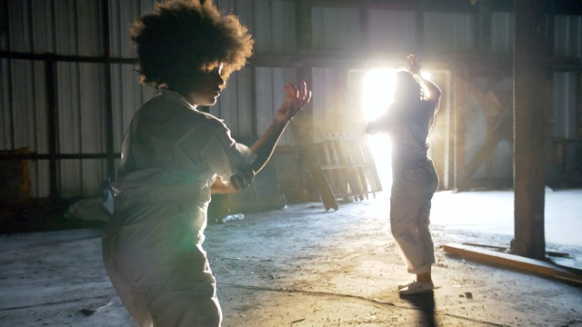two women dancers in white jump suits in an abandoned factory, framed by a bright window