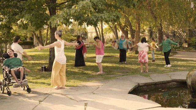 dancers of various ages and abilities, including one in a wheelchair, stretch arms out beside a pond