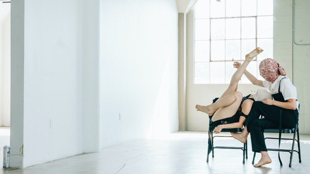 two dancers with faces covered by fabric sit on chairs interweaving their limbs