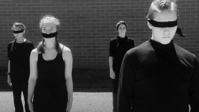 four dancers dressed in black - three blindfolded - stand in front of a brick wall