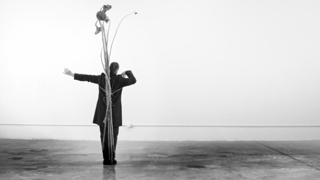a white man in a tux with a sculpture of dead flowers tied to his back