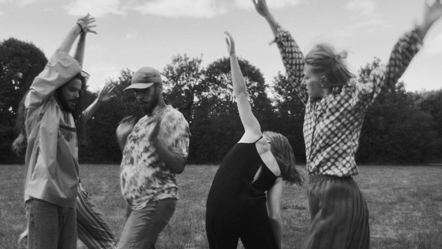 four dancers in a field in black and white fling limbs wildly