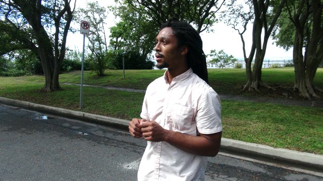 a man with dark skin and dreadlocks in a collared shirt standing on a neighborhood street