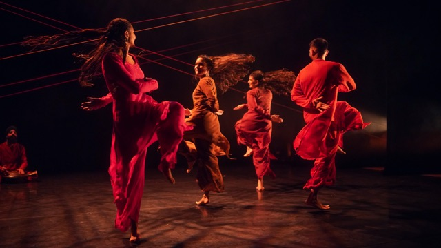 several Indian dancers caught mid turn with fabric and hair flying